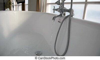 Water flows in white big bathroom. The feeling of...