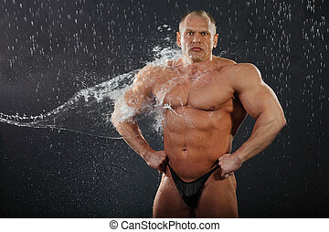 Water flows on undressed tanned bodybuilder in rain. Andrei Popov is Bodybuilding Champion of Russia 2011, up to 90 kg category.