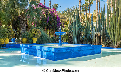 Water fountain in the patio of blue color, a blue fountain of water in the patio