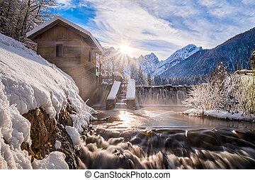 Water from lake Fusine flows over dam in river with mountain...