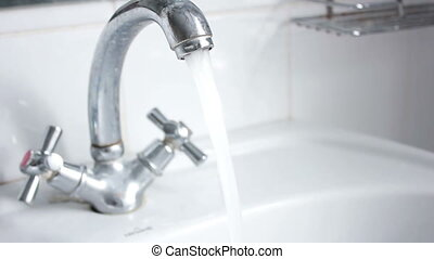 Water from opened faucet - water flows from the tap in the...