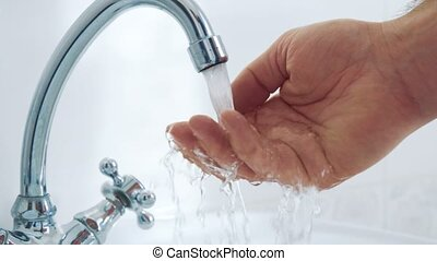 Water from the tap flows to the hand. Slow motion