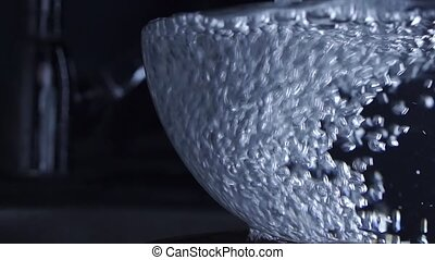 Water from water tap overflowing a glass bowl, slow motion...