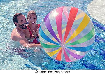 Joyful positive couple playing with a ball