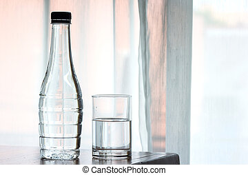 Water glass and bottle on wooden background