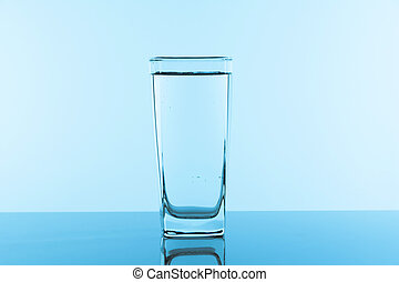 Water glass on blue background. Glass with clean drinking water.