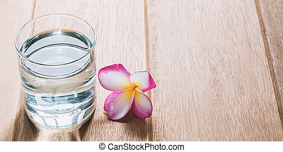 Water glass on wooden table. Glass and clean drinking water with copy space.