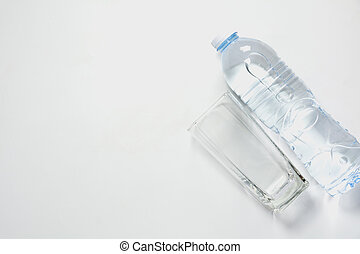 Water glass with bottle on white background with copy space.