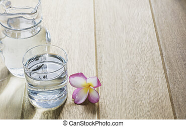Water glass with glass jar on wooden table. Glass and clean drinking water with copy space.