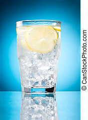 Water glass with lemon and ice isolated on a blue background