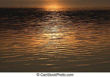 Sunlight path on night sea water.