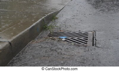 Heavy rainfall on the street. Water goes down a stormdrain.