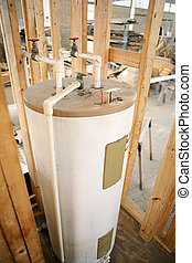 Construction site with hot water heater installed. Focus on center top of water heater.