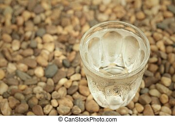 Water in a glass on a background of rock.