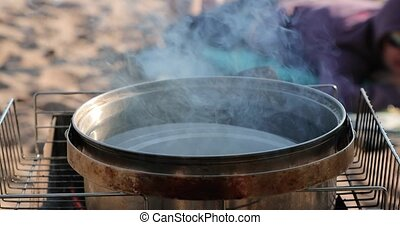 water in a large saucepan is heated at the stake.