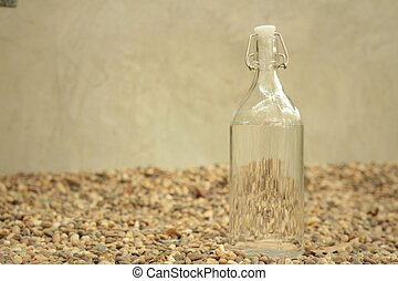 Water in bottle on the background of rocks.