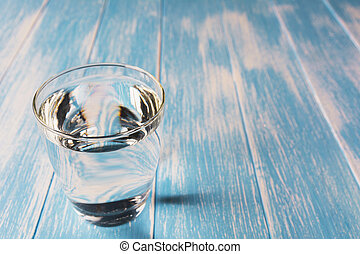 Water in glass on blue and wooden table background.