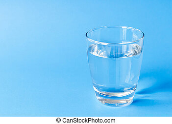 Water in glass on blue background