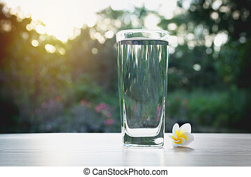 Water in glass with white flower on nature background.