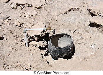 Water in the Desert - Water tap and empty pot in the Desert