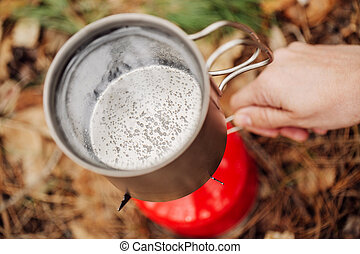 water is boiling in a pot on a gas burner in the forest