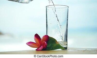 Water is poured into a glass in slow motion next to the frangipani flower and the zen tower on blurred bokeh background. HD, 1920x1080