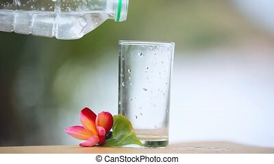 Water is poured into a glass next to the frangipani flower and the zen tower on blurred bokeh background. HD, 1920x1080