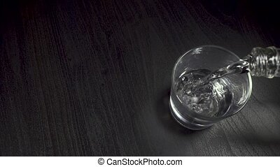 Water is pouring from a bottle into a glass on a table top view slow motion