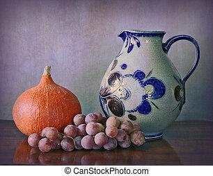 Water jug, pumpkin and grapes