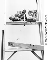 Water level and Blue sneakers on Aluminium ladder with wall dirty , gray color