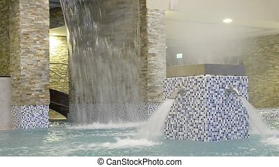 Water massage in empty swimming pool. Decorative waterfall with glass roof