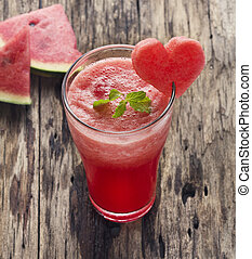 Water melon smoothie and fresh melon on wood background