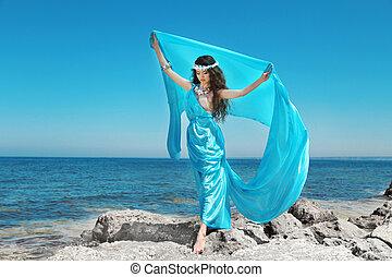 Water Nymph. Beautiful woman in blue chiffon dress embracing over blue sky on beach