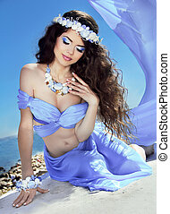 Water Nymph. Long Healthy Hair. Beautiful smiling girl in violet silk luxury dress with sea jewelry.