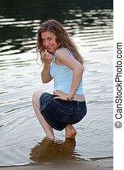 nice girl sit on the beach near river and invite follow her