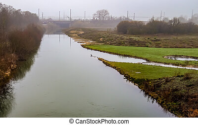 Water of a canal with reflections in the water and a foggy landscape surrounding it