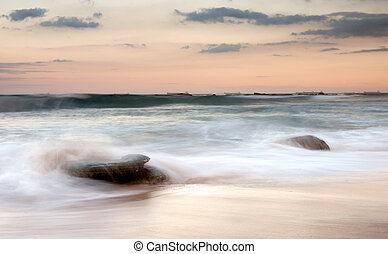 water on rocks at sunset