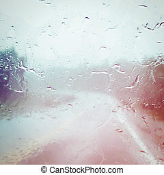 Water on the windshield of car, with view of road with effects