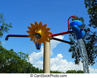 Water Park - A structure in a waterpark sprays and pours ...