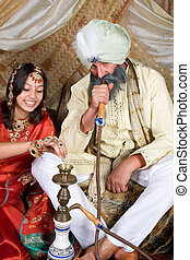 Exotic woman and man demonstrating a water pipe