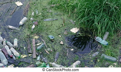 Water pollution. Plastic trash floats in the river.