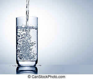 Water pour into glass with reflection on blue grey background