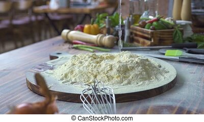 Water pouring in flour for preparation dough in bakery kitchen slow motion. Process making dough for pizza, pasta, spaghetti, pastry on wooden table. Cooking food concept. Baking ingredients on table.