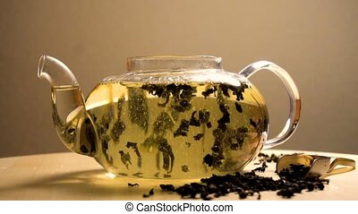 Water pouring in teapot with green tea and became slow
