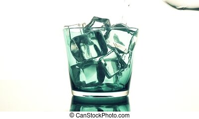 Water pouring into a blue glass with ice cubes