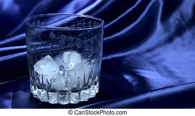 Water pouring into a glass with ice
