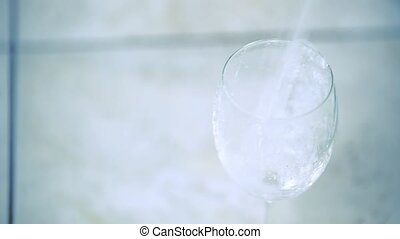 Water pouring into glass and overflowing. Slow motion video...