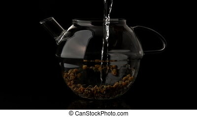 Water pouring into glass teapot over loose herbal tea in...