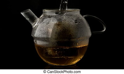 Water pouring into glass teapot over loose tea in slow...