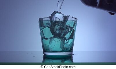 Water pouring into the glass over blue background